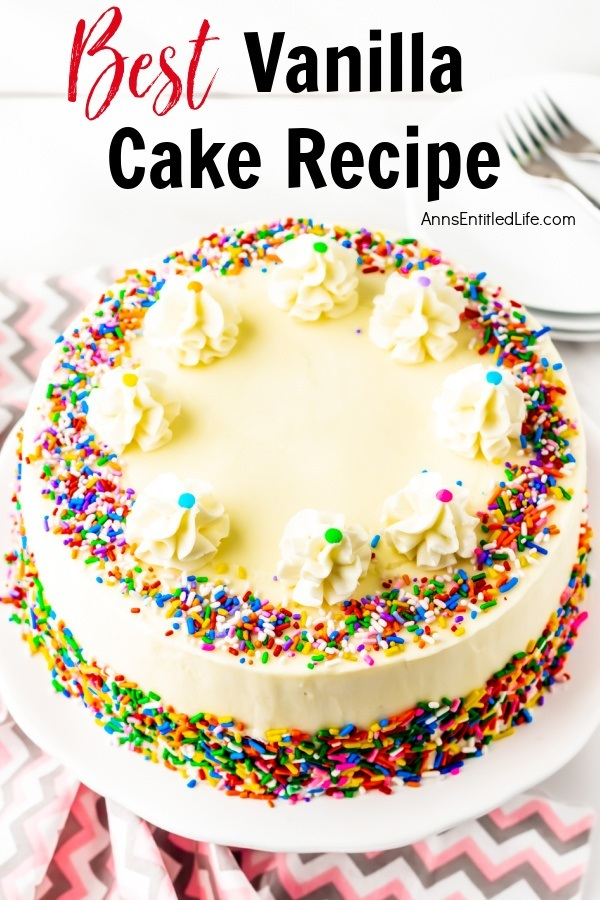 A whole vanilla cake frosted with buttercream frosting, trimmed with ruffle mounds, and decorated with colored sprinkles, on a white cake plate. There is a small stack of white-colored plates and some silverware in the upper right. All this sits on a pink and grey chevron napkin.