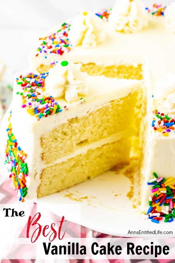 A piece of vanilla cake frosted with buttercream frosting, trimmed with ruffle mounds, and decorated with colored sprinkles is being lifted from the remainder of the cake which sits on a white cake plate. There is a small stack of white-colored plates and some silverware in the upper right. All this sits on a pink and grey chevron napkin.