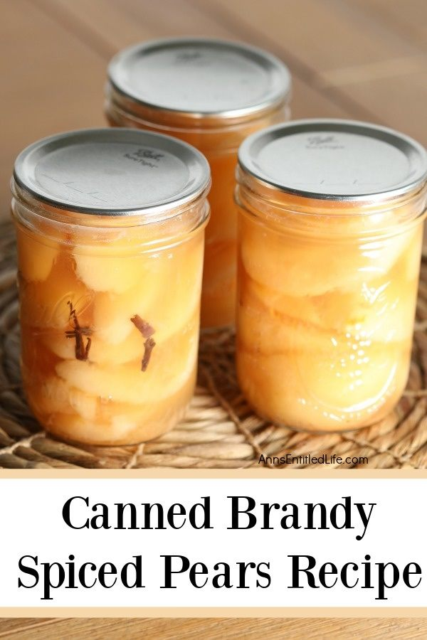 Three jars of canned brandy spiced pears sitting on a rattan placemat
