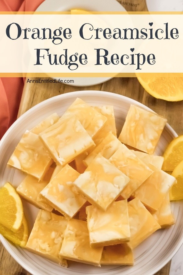 An overhead photo of a white plate filled with cut squares of orange creamsicle fudge. There are orange slice garnishes surrounding the fudge.