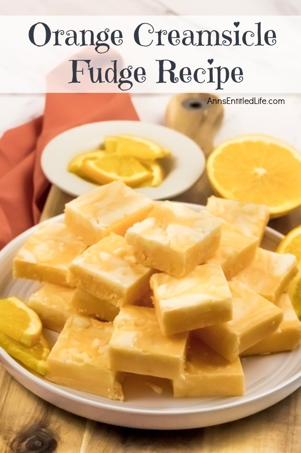 A side view of a white plate filled with cut squares of orange creamsicle fudge. There are orange slice garnishes surrounding the fudge.