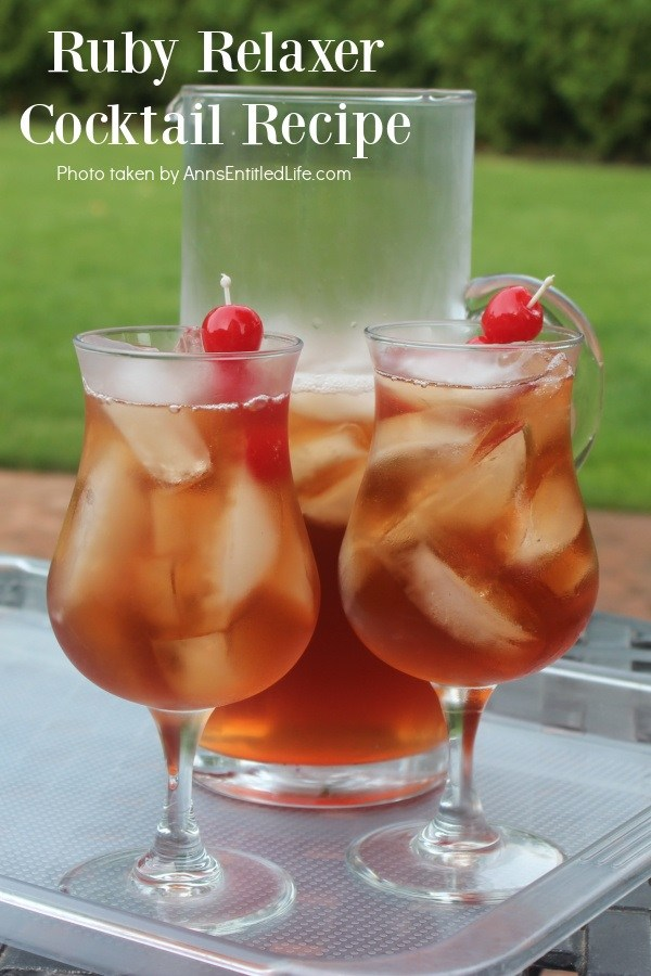 Two glasses and a pitcher of ruby relaxer cocktail set on a plastic tray in a backyard
