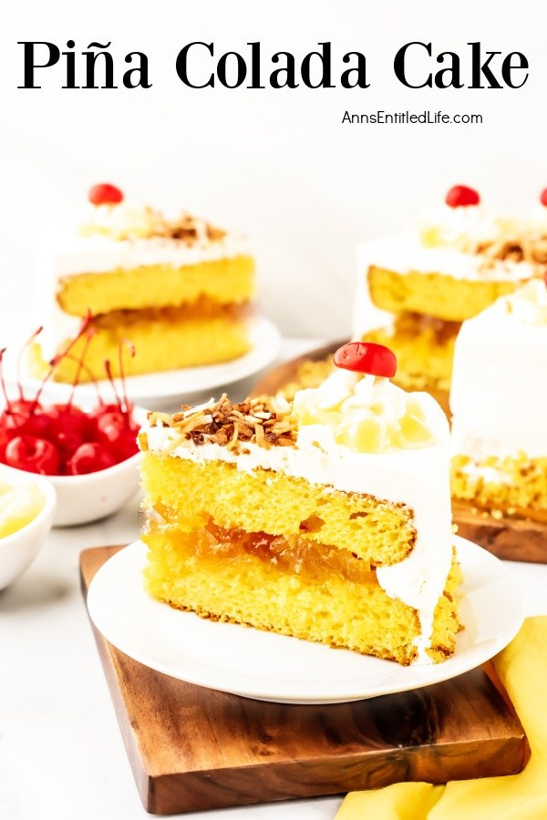 A pina colada cake cut open to show the filling and cake inside sit in the back left, a cut piece of cake sits on aa white plate front and center. There is a second piece in the upper left. A bowl of cherries sits between the two pieces of cake.